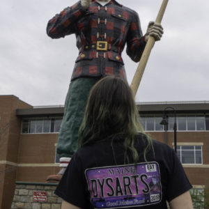 photo of woman wearing dysart's license plate t-shirt in front of paul bunyon