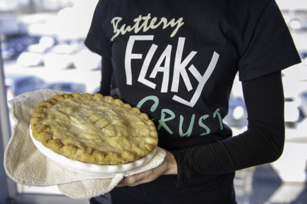 photo of woman holding dysart's pie with buttery flaky crust t-shirt